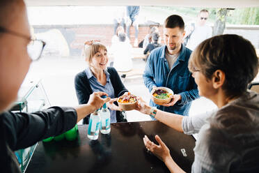 Mature owners serving food and drink to happy customers while standing in commercial land vehicle - MASF16568