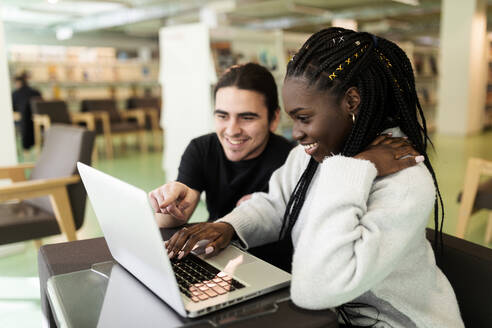 Two smiling students using laptop in a library - VABF02604