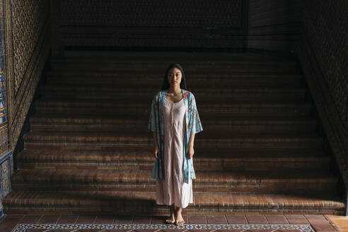 Portait of beautiful young woman wearing a kimono standing at stairs - TCEF00157