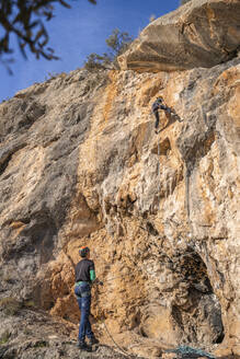 Man securing woman climbing at rock face - DLTSF00447