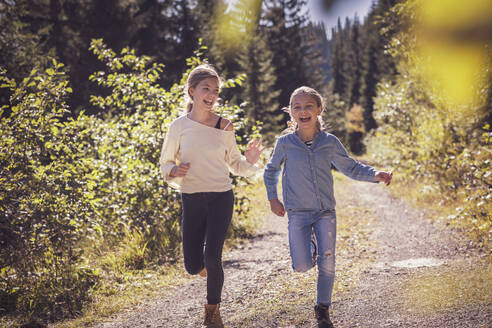 Girls running and having fun on a forest path in the countryside - DHEF00122