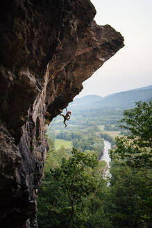 Man climbing overhanging sport climbing route in New Hampshire - CAVF74365