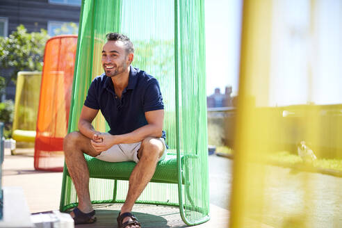 A man sits in a colorful chair on a modern patio. - CAVF74543