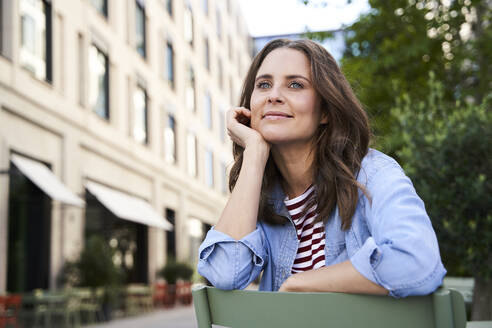 Portrait of smiling brunette woman sitting on a chair in the city - PNEF02235