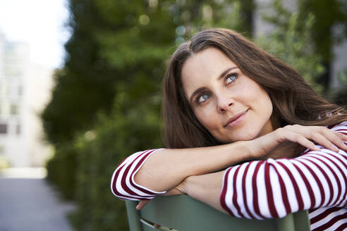 Portrait of daydreaming brunette woman sitting on a chair in the city - PNEF02241