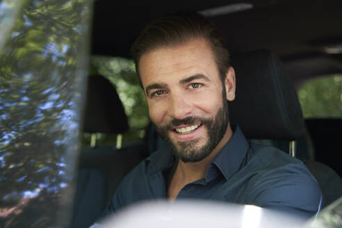 Portrait of smiling man sitting in car - PNEF02262