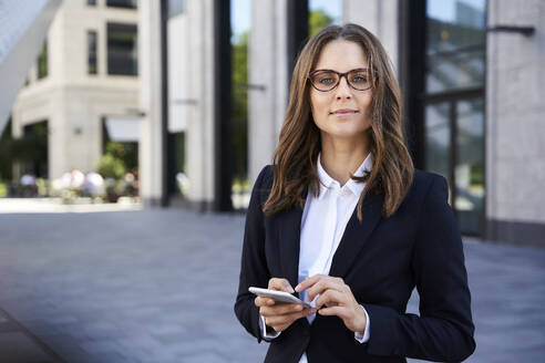 Portrait of confident businesswoman with cell phone in the city - PNEF02271