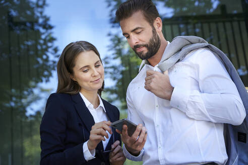 Businessman and businesswoman looking at cell phone in the city - PNEF02289