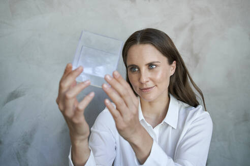 Portrait of confident woman looking at transparant cube - PNEF02307