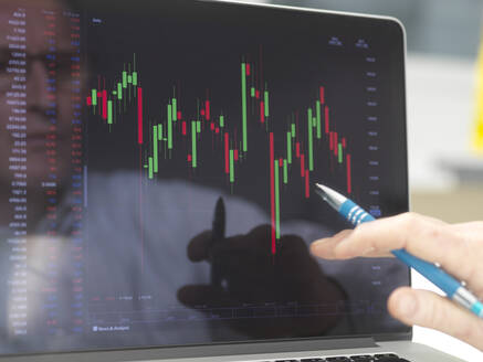 Reflection of a stock trader viewing the performance of a company share price on screen - ABRF00687