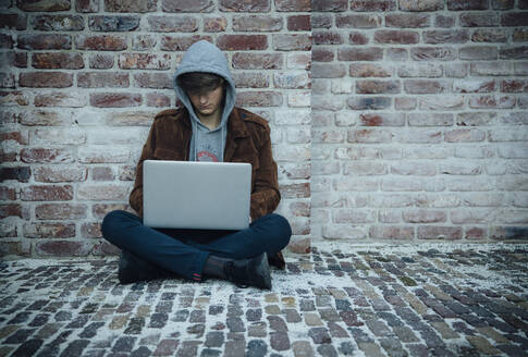 Teenager using laptop and sitting on a stone floor in the city - ANHF00180