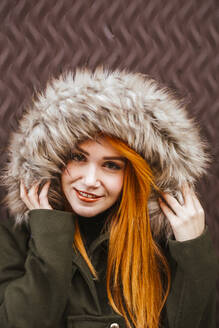 Portrait of smiling redheaded young woman wearing hooded jacket - LJF01292