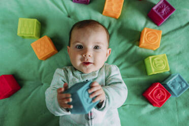 Portrait of baby girl lying on green mat playing with rubber toys - GEMF03420