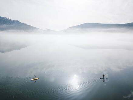 Aerial view of two people stand up paddle surfing, Leon, Spain - DGOF00284