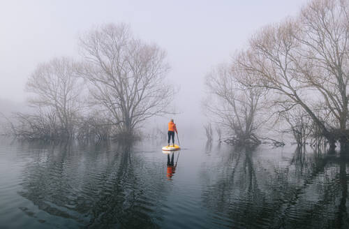 Woman stand up paddle surfing on a lake in the fog - DGOF00305