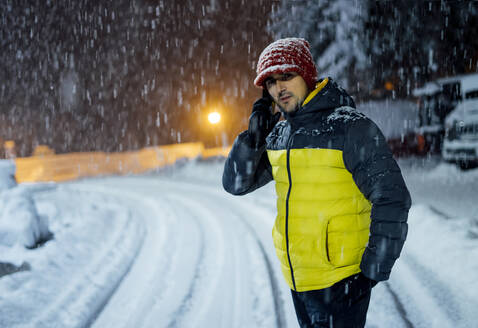 Man on the phone in snowfall at night - CJMF00244