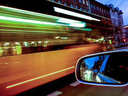 Germany, Berlin, Side mirror of car driving through city at dusk - BIGF00069