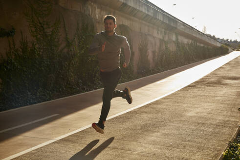 Man running on a road in sunlight - PACF00174