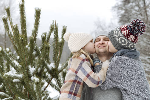 Two kids kissing their happy father at a fir tree in winter - EYAF00928