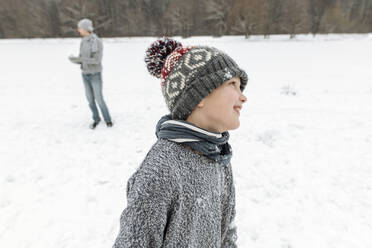 Portait of smiling boy in winter landscape with father in background - EYAF00934