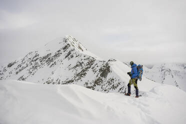 Man on an excursion on the crest of a snowy mountain, Lombardy, Valtellina, Italy - MCVF00221