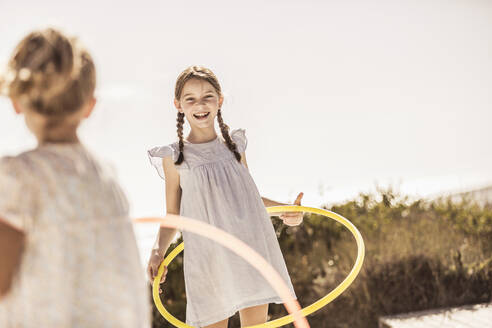 Two happy girls playing with hoola hoop on terrace of a beach house - SDAHF00099