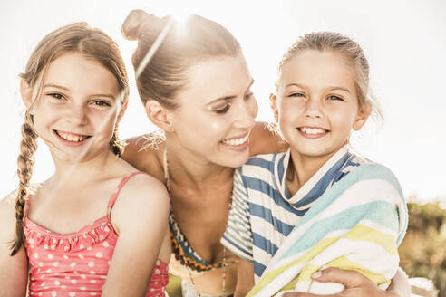 Happy mother caring for her two daughters at the poolside - SDAHF00123