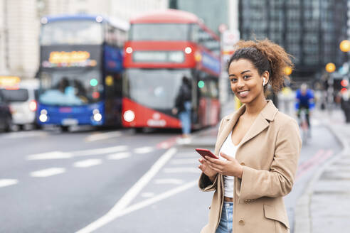 Smiling young woman with cell phone and earbuds in the city, London, UK - WPEF02556