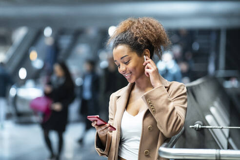 Smiling young woman with cell phone and earbuds at subway station - WPEF02562