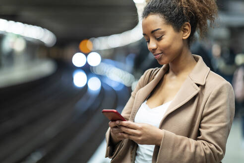 Smiling young woman using cell phone at subway station platform - WPEF02565