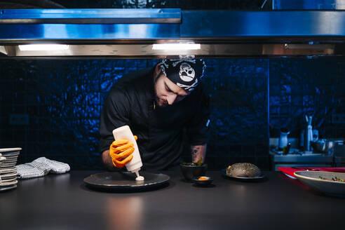 Chef preparing a dish in restaurant kitchen - DGOF00347