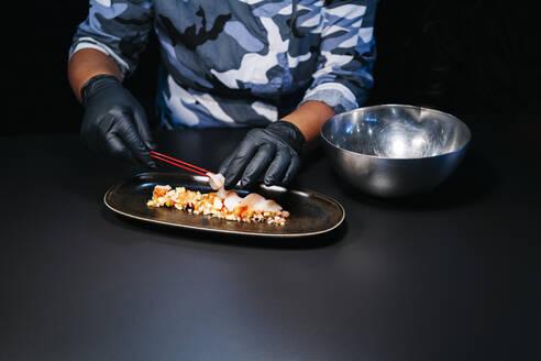 Close-up of chef preparing a dish in restaurant kitchen - DGOF00365