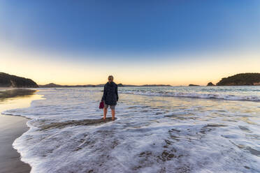 Woman at Hahei Beach during sunrise, Waikato, North Island, New Zealand - SMAF01831