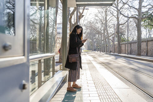 Young woman with smartphone waiting at the tram stop - AFVF05291