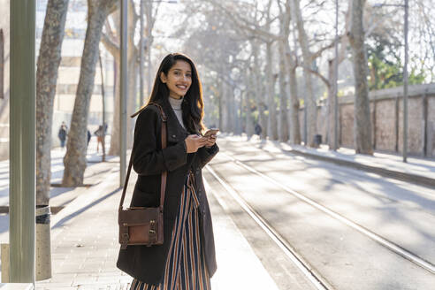 Portrait of smiling young woman with smartphone at the tram stop - AFVF05294