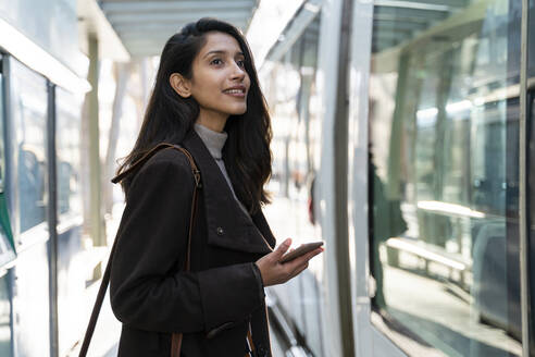 Smiling young woman with smartphone at the tram stop - AFVF05297