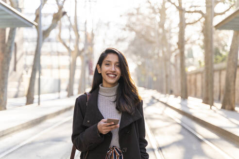 Portrait of smiling young woman with smartphone on tram line - AFVF05300