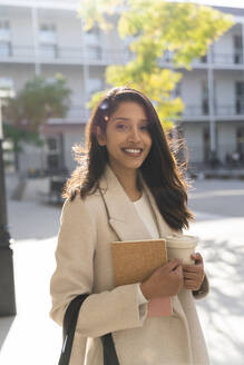 Portrait of smiling young woman with book and takeaway coffee in the city - AFVF05336