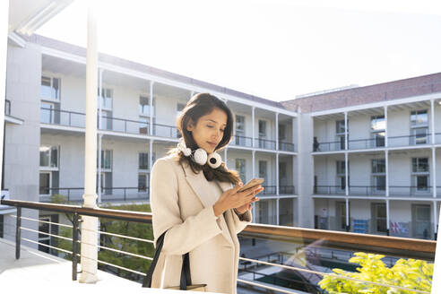 Young woman using smartphone on balcony - AFVF05363