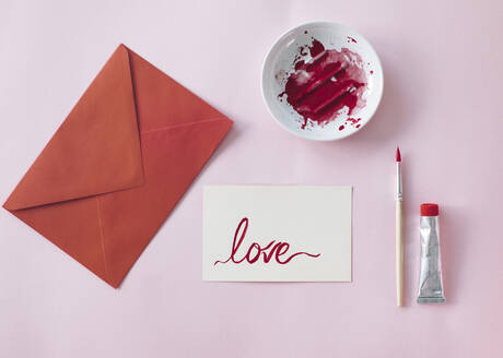 Making a Valetine's day card, red envelope and card with love written on it - MOMF00836