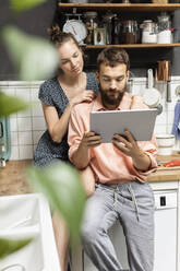 Young couple using digital tablet in kitchen - PESF01786