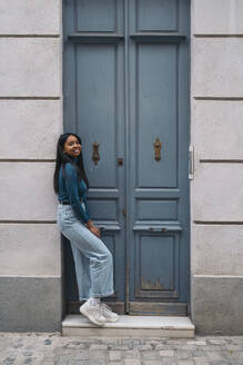Portrait of smiling young woman standing at a door in the city - MPPF00509