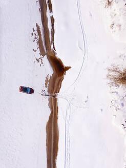 Russia, Leningrad Region,Tikhvin, Aerial view of car in frozen landscape - KNTF04365