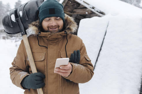 Portrait of smiling man with snow shovel looking at cell phone - KNTF04406