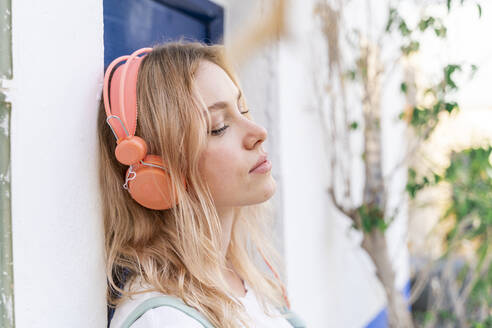 Portrait of young blond woman with eyes closed leaning at facade listening music with headphones - AFVF05424
