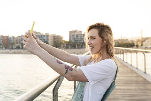 Young woman taking selfie with smartphone, Barcelona, Spain - AFVF05430