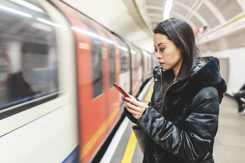 Portrait of woman waiting at underground station platform looking at smartphone, London, UK - WPEF02620