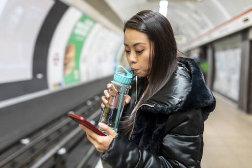 Portrait of woman with drinking bottle and cell phone at underground station platform, London, UK - WPEF02623