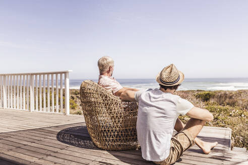 Father and adult son sitting on a terrace at the sea - SDAHF00169