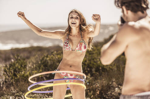 Man taking picture of a young woman playing with hoola hoop - SDAHF00187